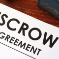 Paper with the words escrow agreement on a table with a pen and a book next to it
