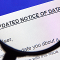 A magnifying glass is placed on a paper press release giving notice to a data breach