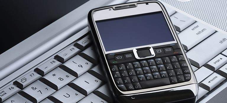 On a keyboard lies a sideways cell phone with a physical key pad, both vulnerable to a data breach