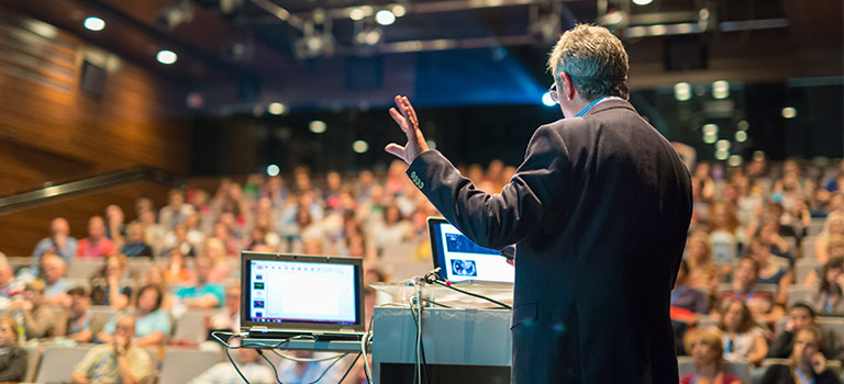 Man speaking at a conference on cybersecurity conferences
