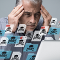 Frustrated Man massages his head in frustration as his laptop is taken over by Malware. Floating files surround him with skull and bones symbols.