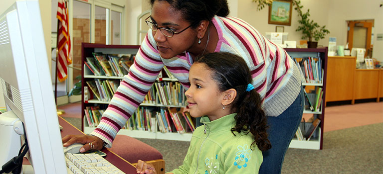 Woman assisting young girl who is typing on a computer in a library child internet safety