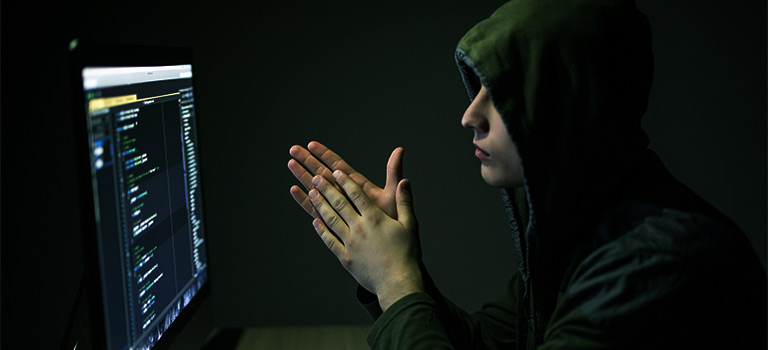 Black Hat Hacker staring at computer screen wearing hoodie as the room is illuminated by green light. White Hat Hacker conceptual.