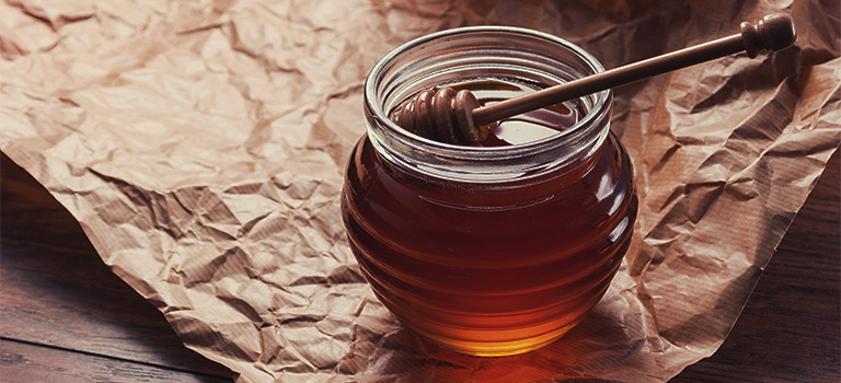 honeypot sitting on a brown paper on a table. Spoon in honey. Honey jar.