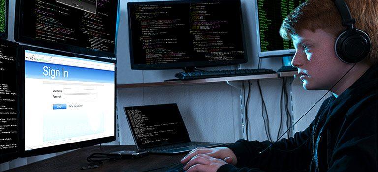 Script Kiddie hacking in a dark room, multi computer set up, young hacker
