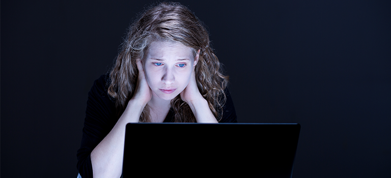 Girl looks sad and scared at computer, victim of cyberstalking, scared of cyberstalkers.
