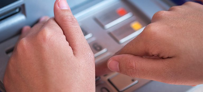 Hand typing in ATM passcode on notepad while covering the keys for privacy, abstract for Card Skimmer