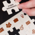 Puzzle piece being placed in a puzzle. The piece is labeled Cyber Insurance.