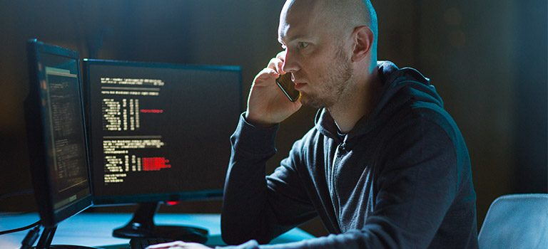 Evil man typing on computer, Insider Threats, cyber criminal.